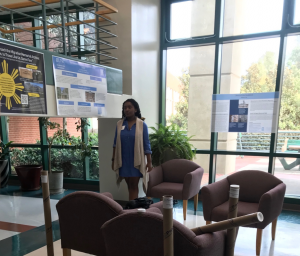 Photograph of ENGL 105i student with conference poster
