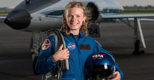 Photograph of Zena Cardman with NASA gear and aircraft